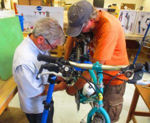 Men working on bicycle at The Hub